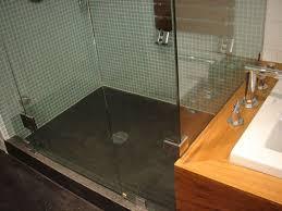bathroom shower with glass door and concrete shower flooring