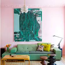 pale pink walls and shots of emerald green artwrk and green sofa
