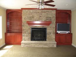 cut stone fireplace custom built cherry wood bookcases wall