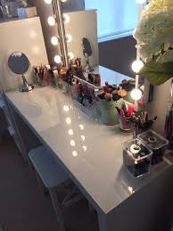 bathroom white wooden makeuo table using lighted mirror plus