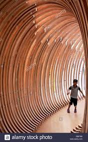 child walking and play inside modern wood sculpture kuwait stock