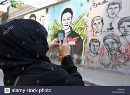 woman takes pictures of a revolutionary mural on a wall of martyrs stock photo woman takes pictures of a revolutionary mural on a wall of martyrs near tahrir square in cairo
