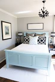 small bedroom using black chandelier over blue bed frame and light