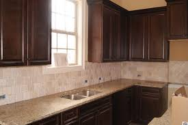 venetian gold light granite venetian gold granite dark cabinets and neutral backsplash