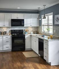 what color of cabinets go with black appliances white cabinetry and a mosaic tile backsplash contrast with