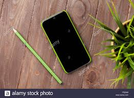 office wooden desk with smartphone and plant top view stock photo