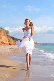 happy in white dress is runnig along sea beach summer warm