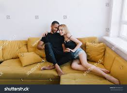 couple hugging eyes closed on couch stock photo 597326573