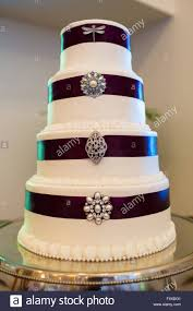 tall white wedding cake wrapped in purple ribbon with brooches