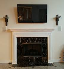 tv mounting over a fireplace with wires concealed in the wall
