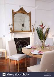 ornate antique gilt mirror above fireplace in contemporary dining