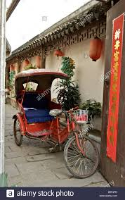 old pedicab parked in small stone floored courtyard off