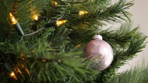 warm yellow bulbs and pink bauble on artificial tree