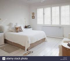 white bedcover on bed in white bedroom with plantation shutters stock photo white bedcover on bed in white bedroom with plantation shutters and white painted wooden flooring