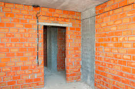 bricklayer building new house with brick walls interior rooms