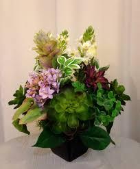 artificial flower and succulent plant arrangement in black ceramic