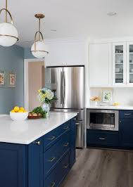 navy blue kitchen cabinet pulls a navy blue center kitchen island is lit by gold and white