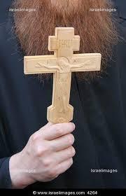 orthodox priest holding a cross at via dolorosa on