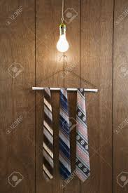 three retro ties hanging on a wire hanger against wood paneling