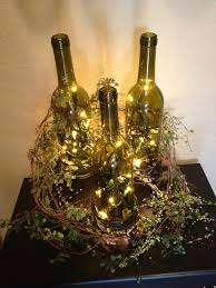 3 wine bottles placed on candle holders of different sizes