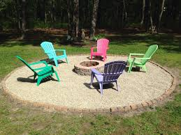 backyard fire pit with pebble rock and adirondack chairs