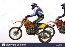 freestyle motocross riders two motocross riders riding along dirt ridge side view front