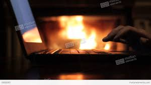 man working with a laptop in front of fireplace close range view