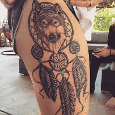 grey ink wolf head dreamcatcher tattoo on side thigh