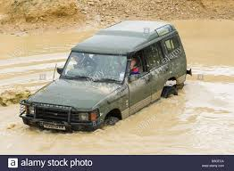 land rover water land rover discovery driving off road through deep muddy water in