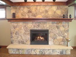 grey stone fireplace with black square fire box on brown floor