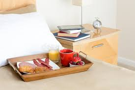 breakfast in bed tray on bed beside night stand stock image