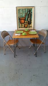 bernard buffet lithograph hangs over a vintage hairpin table and a