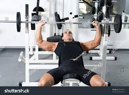 young bodybuilder training gym chest barbell stock photo 69079687