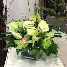 A Flower Vase Classic Creams Greens And White Flower Arrangement In A Clear