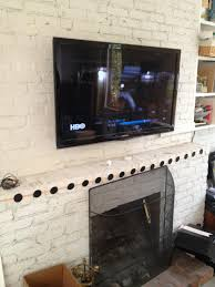 tv mounting over a brick fireplace with wires concealed in wire molding