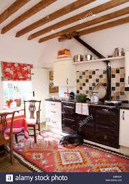 beamed country kitchen with small dog lying on red patterned kelim
