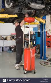 Garage Workshop by Car Mechanic Working In A Garage Workshop Changing The Oil In A