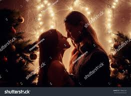 young couple kissing near christmas tree stock photo 519862783