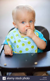 polka dot hair wide eyed baby boy cereal in high chair with polka dot bib