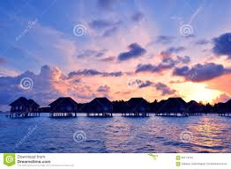 sunrise over water bungalows in maldives stock photo image 63114761