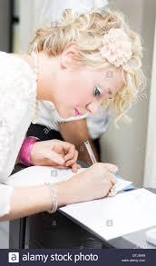 woman wedding guest signs the attendance register book guestbook