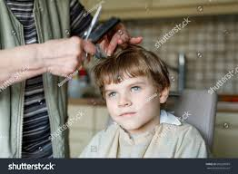 cutting boy hair with scissors beautiful kid boy blond hairs getting stock photo 609228869