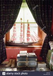 tartan curtains on window with model sailing ship on windowsill in