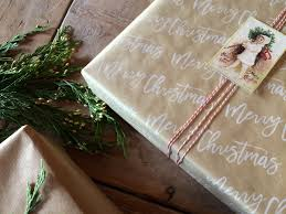present writing paper gift wrapping for christmas along with natural kraft paper we love papers with script writing on them i found this wrapping paper at t j maxx that we embellished with printed tags