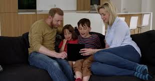family play on tablet in contemporary modern home stock