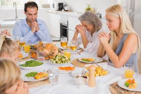 family at thanksgiving dinner family praying before thanksgiving dinner stock photo picture and