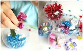 child filling clear plastic ornaments with and flowers