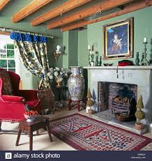 tall chinese pot beside fireplace in pale green cottage living