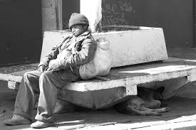 grayscale photo of a man sitting on the concrete bench free image