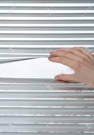 female hand opening metallic venetian blinds for peeking stock